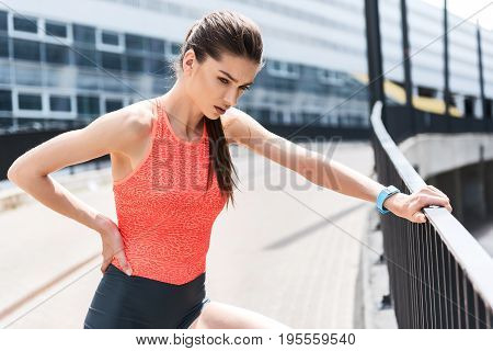 Sad female athlete is suffering from ache in back. She is touching side and looking forward with despair. Girl is standing outdoor and leaning on border