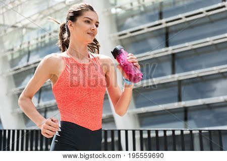 Sport is my life. Portrait of cheerful young woman running and holding bottle of water. She is smiling with happiness. Copy space