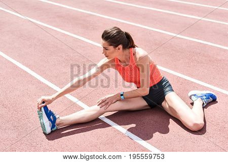 Improving flexibility. Concentrated girl is stretching her leg while sitting on running track in stadium. She is reaching arm to foot with effort