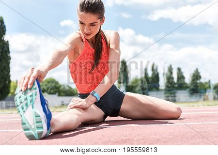 Low angle of serious female runner doing preparatory exercise on stadium. She is sitting and stretching arm to leg. Portrait