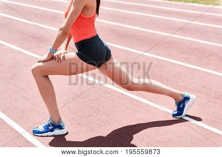 Close up of strong female body standing on running track. Young woman is kneeling and stretching leg aside while warming up
