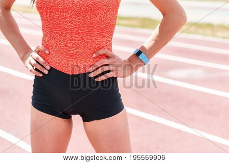 Ready to run. Close up of fit female body. Athlete is standing on running track with arms akimbo