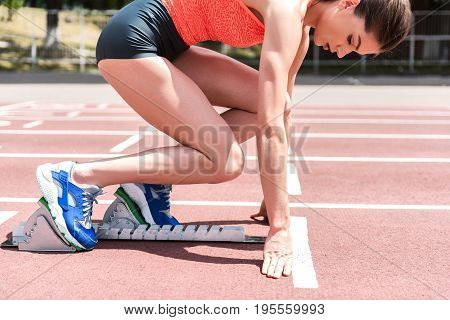 Concentrated young woman is posing in starting block. She is ready for a sprint run on track