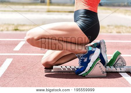 Close up of legs of female sprinter waiting in starting position in the blocks. Girl is kneeling