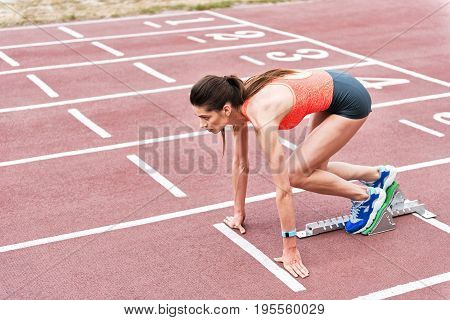 Ready to run. Confident fit girl is standing at starting line in blocks and posing. She is looking forward with aspiration
