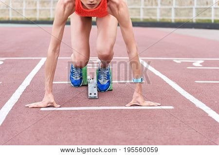 Run. Close up of muscular female arm leaning on track while leaving the starting blocks