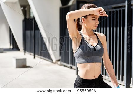 Waist up portrait of tired fit female athlete wiping sweat by hand on forehead after hard training. She is standing and looking aside pensively. Copy space in left side