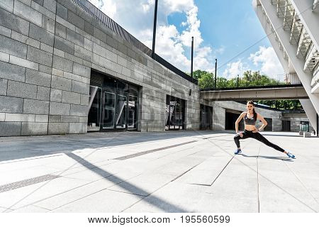 Full length portrait of confident girl doing exercise while standing near stadium. She is stretching leg and keeping arm akimbo. Copy space in left side