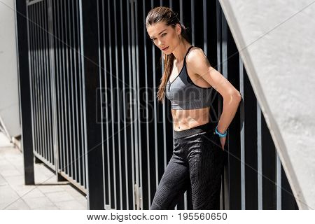 Pensive young sportswoman is resting after training. She is standing and leaning back on fence outdoors. Copy space in left side