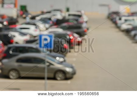 Blurred outdoor parking next to modern shopping mall, sunny summer day, season sales. With place for your text, for background use