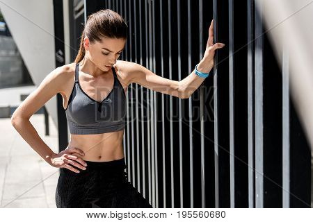 Portrait upset young woman is dissatisfied with results of her training. She is looking down with shame while standing with arm akimbo outdoors
