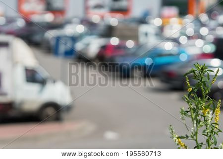 Blurred outdoor parking next to modern shopping mall, sunny summer day, season sales, for abstract background use.