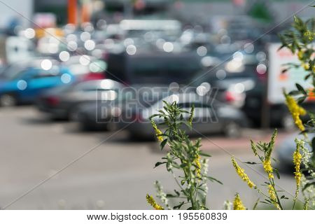 Abstract blurred outdoor parking next to modern shopping mall, sunny summer day, season sales, for background use.