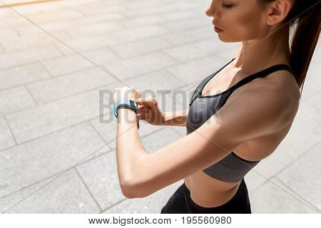 It is time for training. Top view of serious young woman looking at her tracker on arm with confidence. She is standing outdoors. Copy space