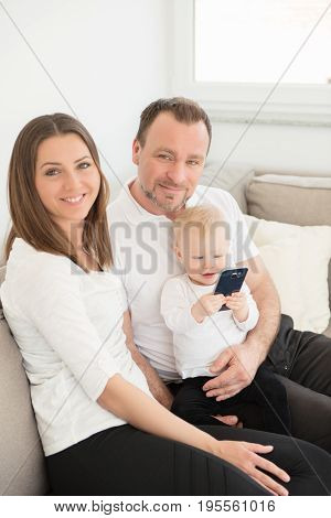 Happy Family Of Three  Is Enjoying At Home. Parents And Their Beautiful Baby Girl Sitting On The Sof