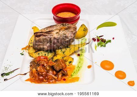 Side view bovine meat with potato and sauce decorated in white plate. Restaurant meal.