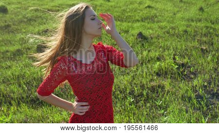 girl nature wind. girl woman is standing in field of grass green. lifestyle woman freedom