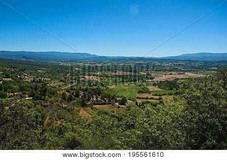 Panoramic view of the fields and hills of Provence near Gordes, under sunny blue sky. Located in the Vaucluse department, Provence region, in southeastern France