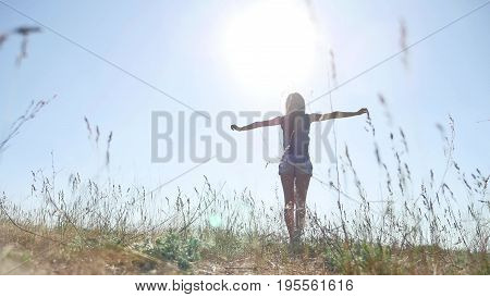 travel. Girl Young woman arms raised enjoying fresh air in grass sunlight nature