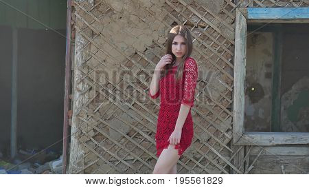 Beautiful girl in a red dress. Sexy girl in a dress is standing next to the old house of ruins lifestyle