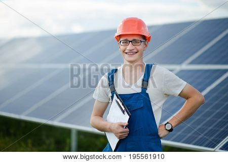 Worker in helmet standing, solar panels behind him. Young man in blue overall, helmet, glasses, holding folder with papers.