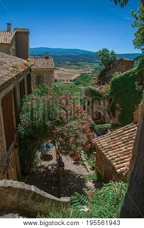 Panoramic view of the fields and hills of Provence in the lovely Gordes village, with stone houses and flowering trees. Vaucluse department, Provence region, southeastern France