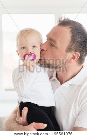 Portrait Of Happy Father Kissing His Daughter. Family Values. Leisure Together. Baby Girl With Pacif
