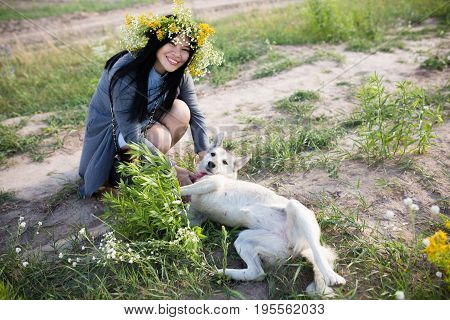 Dog owner playing with her favorite dog. Beautiful oriental young woman wearing fower wreath walking with dog.