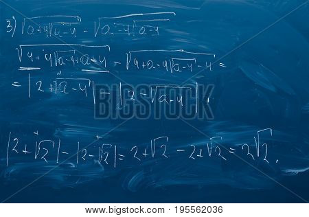 Blue blackboard with the solution of math assignment. Chalkboard wooden isolated Closeup. Horizontal Image