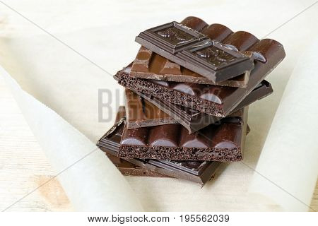 Chocolate Bar Black, Milky, Porous Chocolate Stacked On A Parchment Paper And A Wooden Board. Chocol