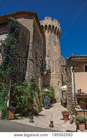 View of stone houses, castle tower and narrow alley in the historical city center of Gordes. Located in the Vaucluse department, Provence region, in southeastern France