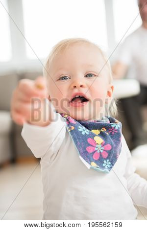 Portrait Of Nicely Dressed And Happy Baby Girl Pointing With Finger.