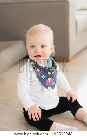 Nicely Dressed And Happy Baby Girl With Blue Eyes Sitting On The Ground.