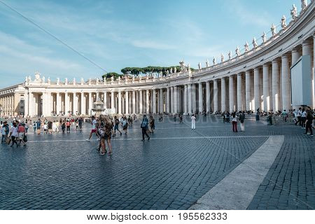 Rome Italy - August 19 2016: St Peters Square with a crowd of tourists a summer day. It is located directly in front of St. Peter's Basilica in the Vatican City and was designed by Bernini