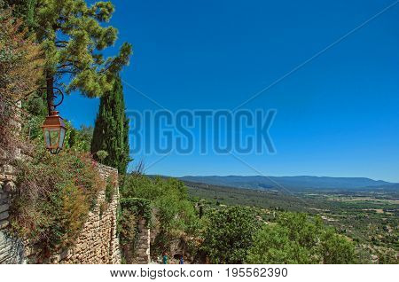 Gordes, France - July 03, 2016. View of the fields and hills of Provence near Gordes, under sunny blue sky. Located in the Vaucluse department, Provence region, southeastern France