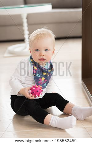 Nicely Dressed And Happy Baby Girl With Blue Eyes Sitting On The Ground And Playing With Ball.