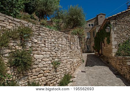 View of typical stone houses with sunny blue sky, in an alley of the historical city center of Gordes. Located in the Vaucluse department, Provence region, southeastern France
