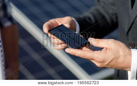 Close up view on photovoltaic elements of solar panel. Business client holding photovoltaic element in his hands.