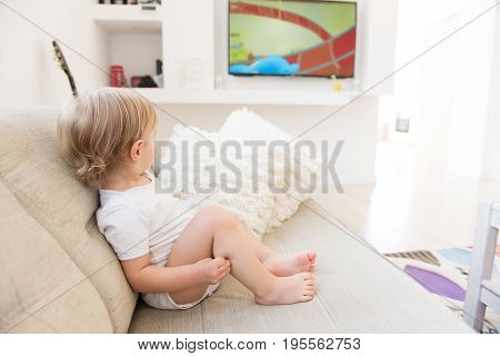 Cute Baby Boy Sitting And Watching Cartoons.