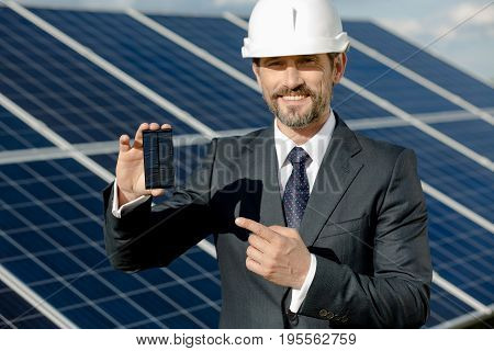 Business client showing photovoltaic detail of solar panel. Man in business suit and white helmet at solar energy station.