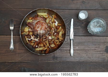 dinner with pan fried meat and potatoes on a wooden table