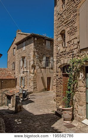 Gordes, France - July 03, 2016. View of typical stone houses with sunny blue sky, in an alley of the historical city center of Gordes. In the Vaucluse department, Provence region, southeastern France