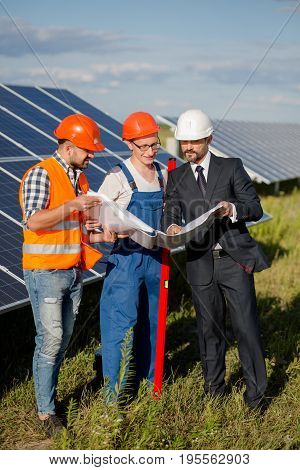 Business client, foreman and worker at solar energy station. Workers and client discussing technical aspects of solar panel.