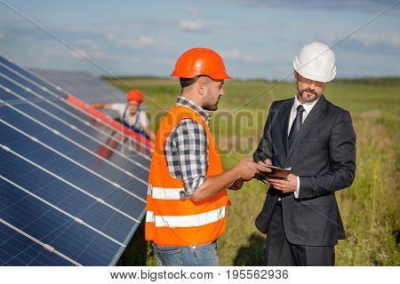 Businessman signing contract with foreman, technician examining solar panels at backdrop. Signing of agreement at solar energy station in the field.