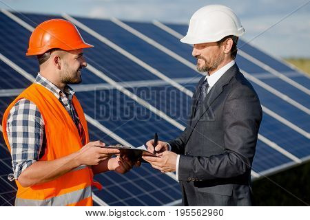 Client and foreman signing contract on installation of solar panels. Order and foreman discussing technical aspects and signing documents.