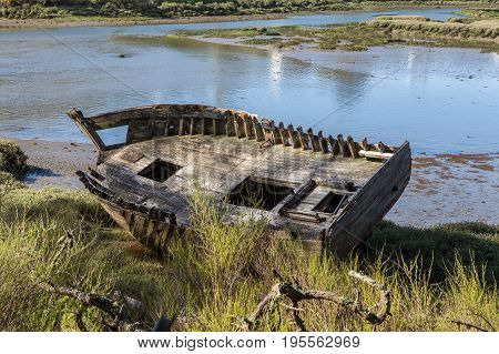 Old wooden boat washed ashore at a sea lagoon estuary