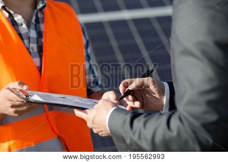 Close up view on foreman and client sigining contract at solar power station. Agreement signing between worker and businessman, solar energy panels on backdrop.