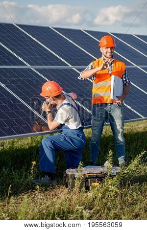 Engineer with drill installing solar power panels. Employee working with drill and foreman showing ok with his fingers.