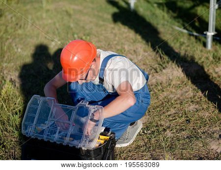 Engineer checking his toolbox. Worker preparing for installation of solar energy panels,