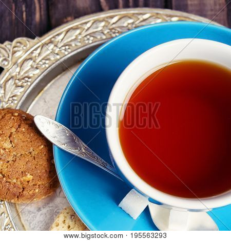 Blue cup of tea and cookies on a silver salver